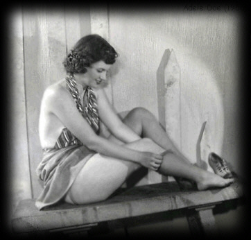 Miss Adele Doe Photo of Burlesque Stripper Dancer: circa 1950's. Dancer is adjusting rolled Black Knee High stockings with no garters., a skirt, top, shoes off and sitting on a bench.