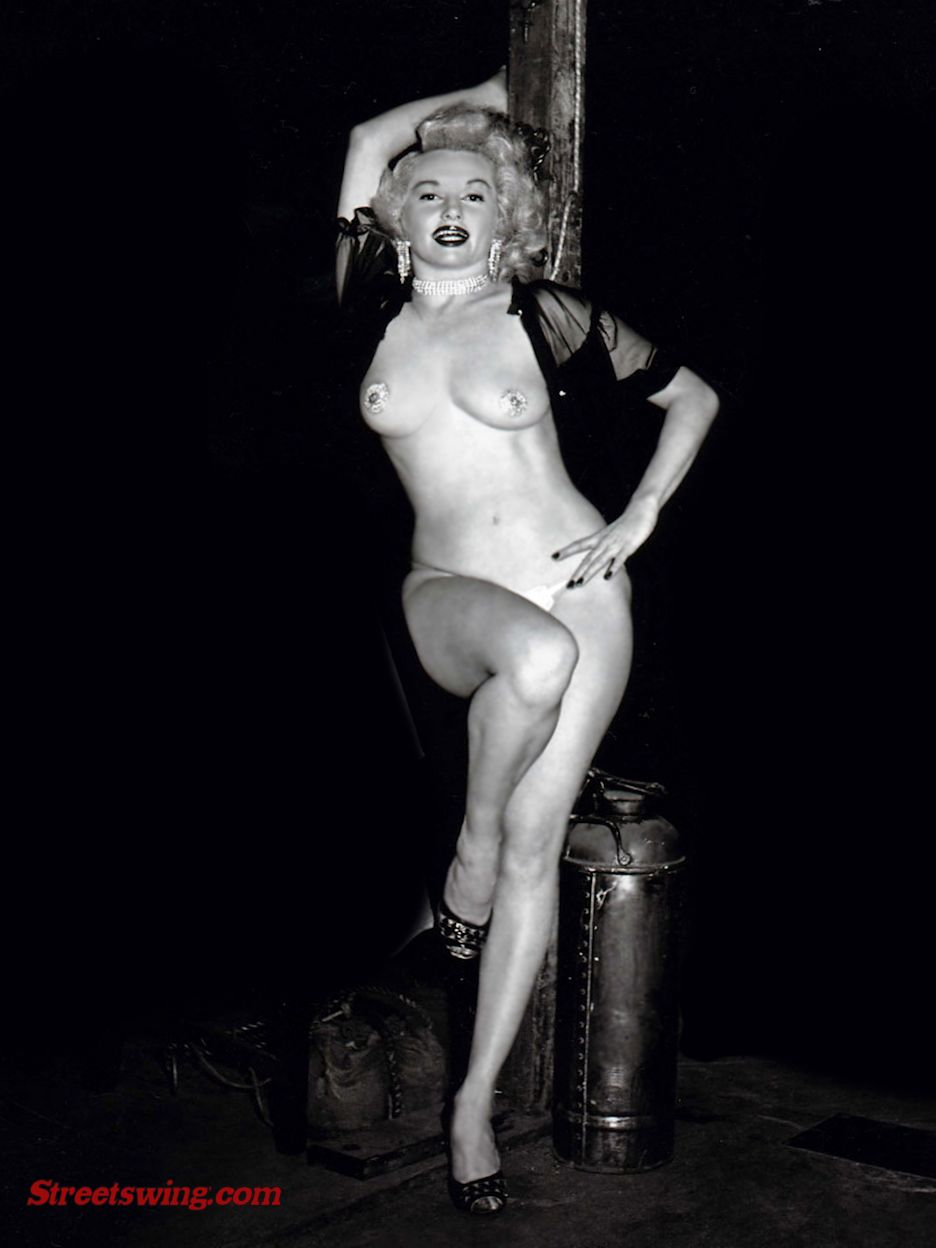 Dixie Evans - Burlesque dance star - Posing outdoors against a sign post, scantily dressed with pasties