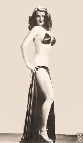 Burlesque Dancer, Stripper  Betty '(Blue Eyes)' Howard  aka 'The Girl Who Has Everything'  Black and White Promo of Betty standing sideways in her black satin costume.  (Harold Minsky, billed her as among the world's top ten exotic performers.)