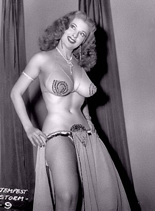 Tempest Storm - Black and White photo of Red Headed Burlesque Dancer, Stripper. Wearing a veiled sheer dress and top with pasties and necklace. Only Burlesque Dancer to dance at Carnegie Hall