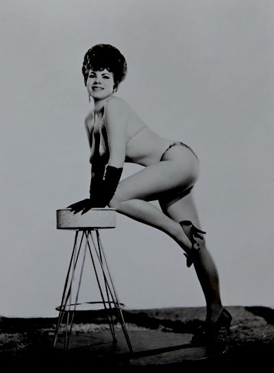 "Burlesque dancer ""Gee Whizz"" in bikini leaning on bar stool"
